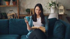 Atrakcyjna dziewczyna jest czytelniczej książki obsiadaniem na kanapie z filiżanką cieszy się pokój i samotność w domu herbaciani zbiory