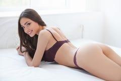 Atrakcyjna dziewczyna na łóżku. Piękne młode kobiety kłama na kanapie Obraz Stock