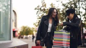 Atrakcyjna dziewczyna outdoors wtedy spotyka jej przyjaciela wybiera odziewa od sklepowej nadokiennej pozyci, młode kobiety ścisk zdjęcie wideo