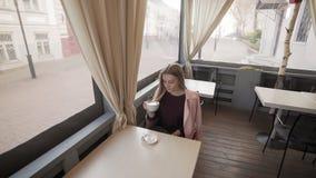 Atrakcyjna dziewczyna pije kawę w kawiarni podczas przerwy kubki kobieta zbiory wideo