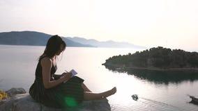 Atrakcyjna dziewczyna pisze w notesie siedzÄ…cym wysoko na skale nad morzem zbiory wideo