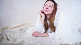 Atrakcyjna dziewczyna pozuje i ono uśmiecha się, wysyłający lotniczego buziaka, kłama na podłoga zakrywającej koc w jaskrawym pok zdjęcie wideo
