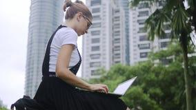 Atrakcyjna dziewczyna pracuje na laptopie outdoors zbiory wideo