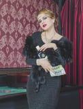 Atrakcyjna dziewczyna przy kasynem z pieniądze i butelką Obrazy Stock