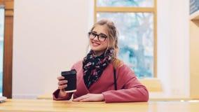 Atrakcyjna dziewczyna stoi kawowego baru czekaniem dla jej rozkazu z przypadkową fryzurą i eleganckimi szkłami, samiec zbiory wideo