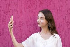 Atrakcyjna dziewczyna używa telefon komórkowego dla zabawy Fotografia Royalty Free