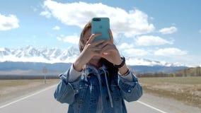 Atrakcyjna dziewczyna w cajg kurtce bierze fotografie góry na telefonie 20s 4k zdjęcie wideo