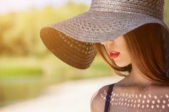 Atrakcyjna dziewczyna w czarnym kapeluszu będącym ubranym na głowie na plaży, Obraz Royalty Free