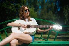 Atrakcyjna dziewczyna w okularach przeciwsłonecznych bawić się białą gitarę zdjęcie stock