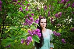 Atrakcyjna dziewczyna w parku przeciw kwiatonośnemu drzewu Obraz Stock