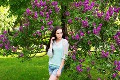 Atrakcyjna dziewczyna w parku przeciw kwiatonośnemu drzewu Zdjęcia Stock
