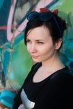 Atrakcyjna dziewczyna w skórzanej kurtce pozuje przeciw tłu szorstkie ściany malował w graffiti rysunkach zdjęcia royalty free