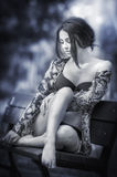 Atrakcyjna dziewczyna w swimsuit obsiadaniu relaksował na ławce Modny kobieta model z romantycznym spojrzeniem pozuje w parku pię Obraz Royalty Free