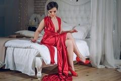 Atrakcyjna dziewczyna w wieczór czerwieni sukni i czerwień butach w sypialni dziewczyna siedzi na łóżku i prostuje suknię w ch fotografia stock