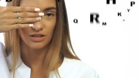Atrakcyjna dziewczyna z brązów oczami sprawdza wzrok w oftalmologu odizolowywającym na białym tle zbiory wideo