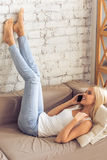 Atrakcyjna dziewczyna z gadżetem w domu zdjęcia stock