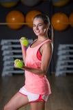 Atrakcyjna dziewczyna z kolorowymi dumbbells na gym tle Fenomenalna kobieta z perfect ciałem w gym fotografia stock