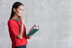 Atrakcyjna elegancka dziewczyna czyta pensively zdjęcia stock