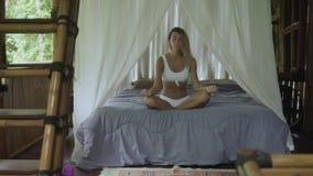 Atrakcyjna Europejska młoda kobieta medytuje na hotelowym łóżku, medytacyjna blondynka w egzotycznym pokoju budującym bambus zbiory