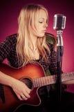 Atrakcyjna kobieta bawić się gitarę akustyczną Obrazy Royalty Free