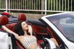 Atrakcyjna kobieta blisko odwracalnego samochodu Zdjęcia Royalty Free