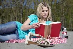 Atrakcyjna kobieta czyta książkę na plaży Fotografia Stock