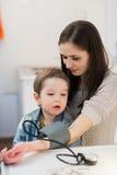 Atrakcyjna kobieta i jej dzieciak z ciśnienie krwi metru tonometer zdjęcia royalty free