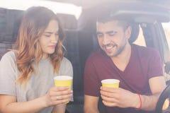 Atrakcyjna kobieta i nieogolona męska para kawową przerwę w samochodzie, zasięg miejsce przeznaczenia z wysoką prędkością Szczęśl zdjęcia stock