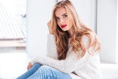 Atrakcyjna kobieta jest ubranym pulower i czerwieni pomadkę patrzeje kamerę Fotografia Stock