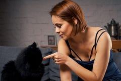 Atrakcyjna kobieta na leżance z czarnym kotem Zdjęcie Royalty Free