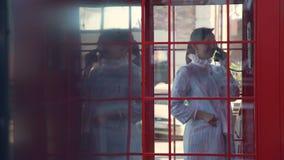 Atrakcyjna kobieta opowiada na telefonie w telefonu budka zbiory