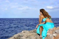 Atrakcyjna kobieta patrzeje dennego horyzont rozważnego od rockowej falezy wewnątrz relaksuje pojęcie Fotografia Royalty Free