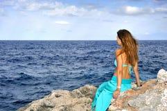 Atrakcyjna kobieta patrzeje dennego horyzont rozważnego od rockowej falezy wewnątrz relaksuje pojęcie Fotografia Stock