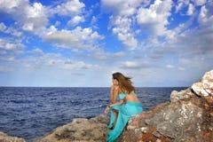 Atrakcyjna kobieta patrzeje dennego horyzont rozważnego od rockowej falezy wewnątrz relaksuje pojęcie Zdjęcia Stock