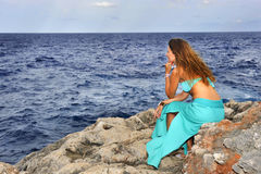 Atrakcyjna kobieta patrzeje dennego horyzont rozważnego od rockowej falezy wewnątrz relaksuje pojęcie Obrazy Royalty Free