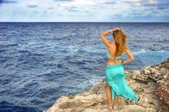 Atrakcyjna kobieta patrzeje dennego horyzontu pozycję na rockowej falezie zdjęcia royalty free