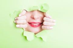 Atrakcyjna kobieta pokazuje pięknego uśmiech przez poszarpanego zielonego cardboa obrazy royalty free