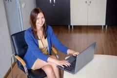 Atrakcyjna kobieta pracuje na laptopie w uruchomienia biurze obrazy stock