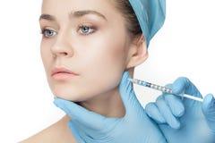 Atrakcyjna kobieta przy chirurgią plastyczną z strzykawką w jej twarzy obraz royalty free