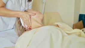 Atrakcyjna kobieta przy zdrojów zdrowie klubem dostaje twarzowego masaż i procedurę Zdjęcia Royalty Free