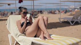 Atrakcyjna kobieta relaksuje app na smartphone i używa w okularach przeciwsłonecznych zbiory