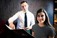 Atrakcyjna kobieta rozkazuje kelner od menu Zdjęcia Stock