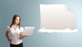 Atrakcyjna kobieta trzyma laptop i przedstawia nowożytnego odbitkowego zdrój Zdjęcie Royalty Free