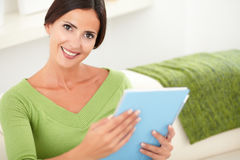 Atrakcyjna kobieta trzyma pastylkę indoors Obrazy Royalty Free