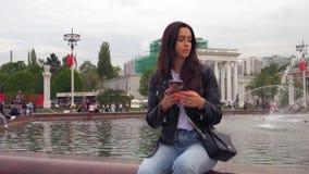 Atrakcyjna kobieta używa telefon komórkowego w parku podczas gdy chodzący Ultra HD materia? filmowy zbiory wideo