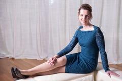 Atrakcyjna kobieta w błękit sukni obsiadaniu na leżance zdjęcie royalty free