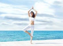 Atrakcyjna kobieta w biały sporty odziewa robić joga na drewnianym Obraz Royalty Free