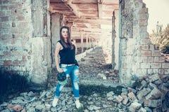 Atrakcyjna kobieta w cajgu i filiżanki stroju pozuje w starym rujnującym fabryka domu Zdjęcie Stock