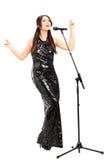Atrakcyjna kobieta w czerni sukni śpiewie Zdjęcie Royalty Free