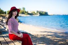 Atrakcyjna kobieta w czerwonym obsiadaniu na plaży fotografia royalty free